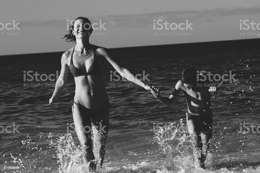 Mother and son running from the water stock photo