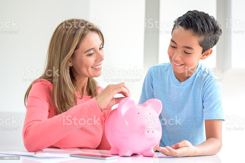 Mother and son saving money in a piggybank stock photo