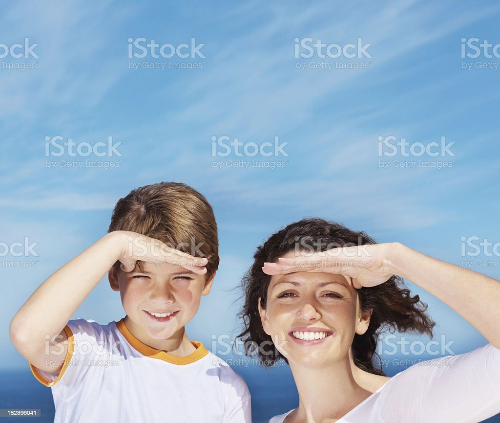Mother and son shielding eyes while outdoors royalty-free stock photo