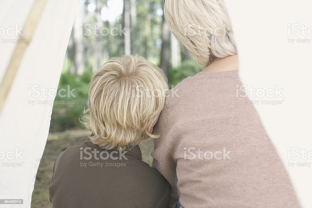 Mother and son sitting in tent royalty-free stock photo