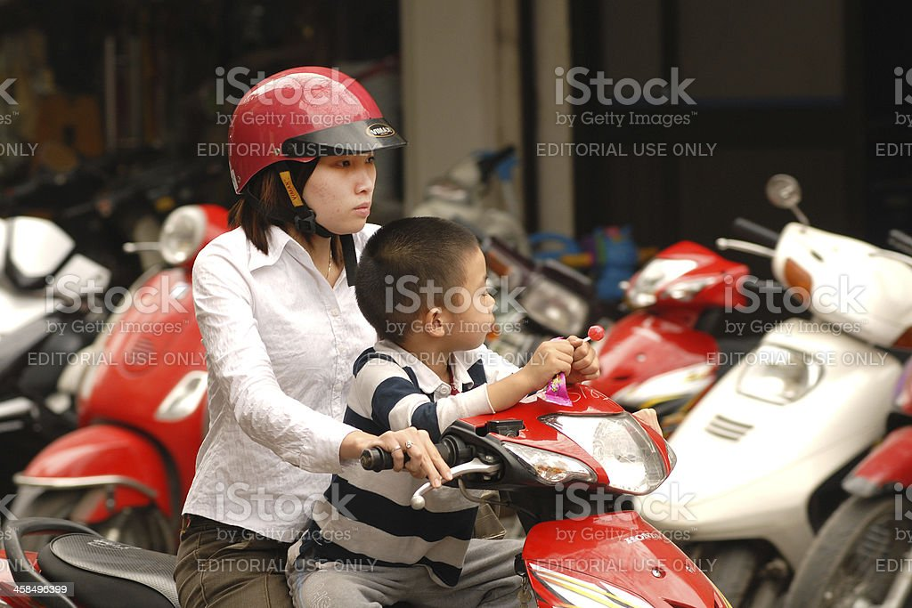 Mother and son sitting on a motor scooter, Hanoi, Vietnam royalty-free stock photo