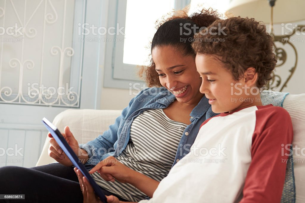 Mother And Son Sitting On Sofa Using Digital Tablet stock photo