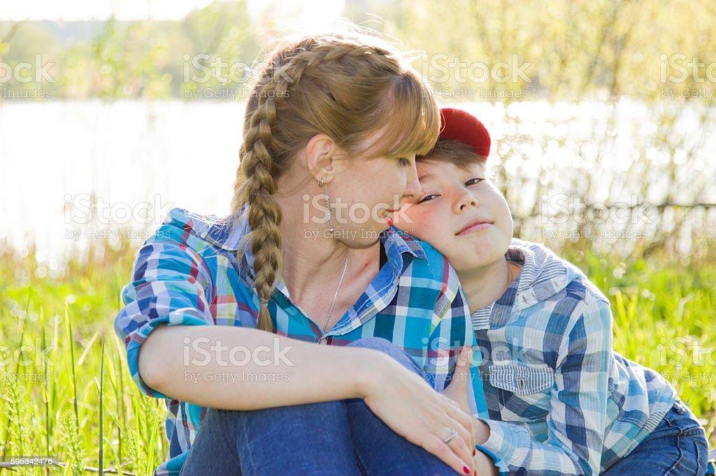 Mother and son sitting on the grass stock photo