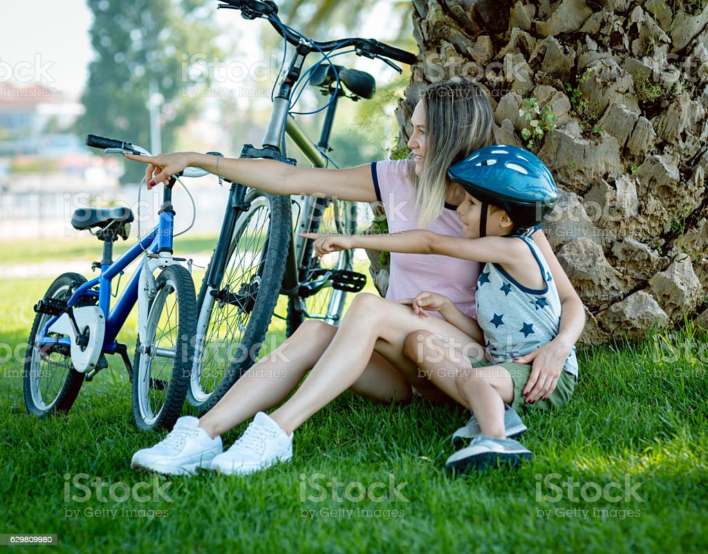 Mother and son sitting on the grass with rented bicycle stock photo