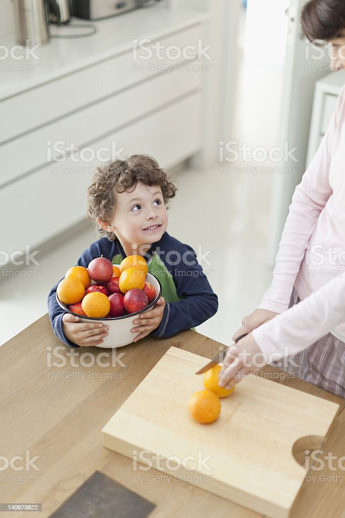 Mother and son slicing fruit in kitchen stock photo