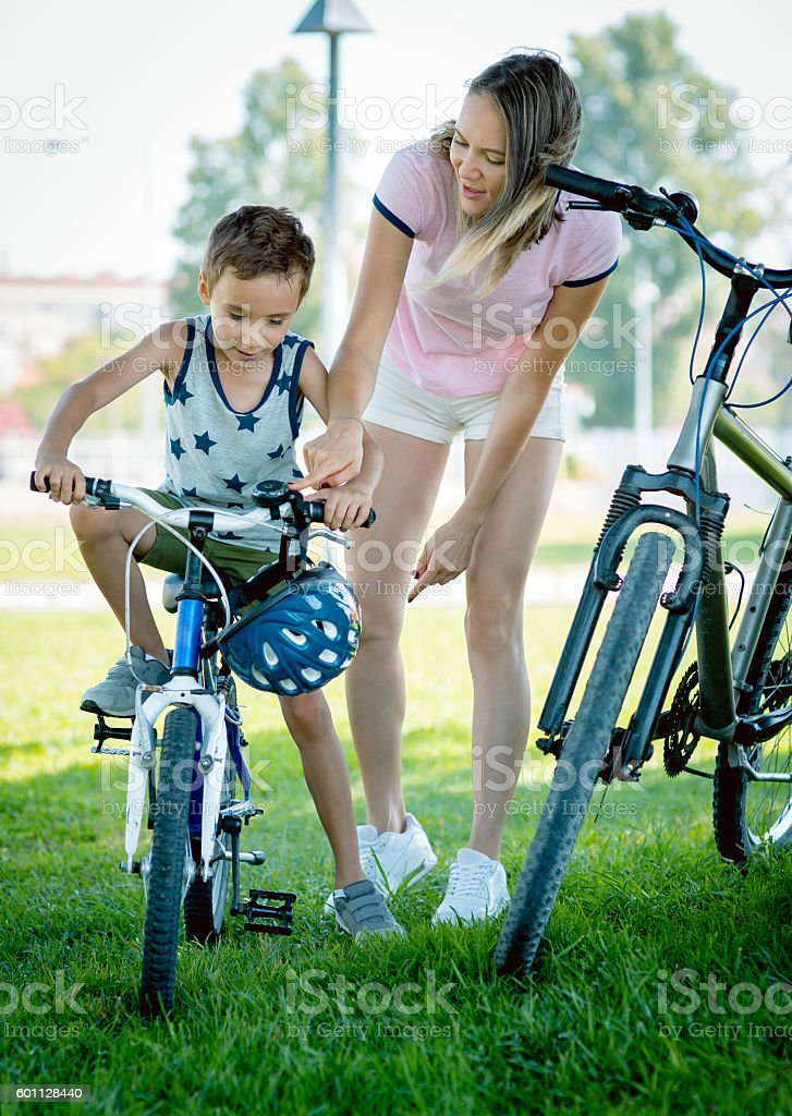 Mother and son standing on the grass with rented bicycle stock photo