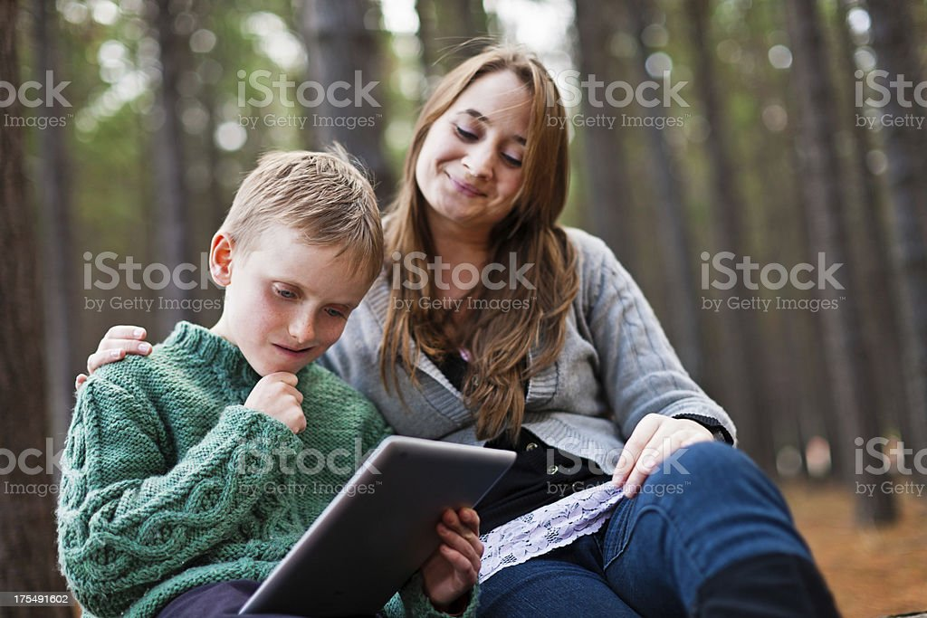Mother and son study tablet-style personal computer together in forest stock photo