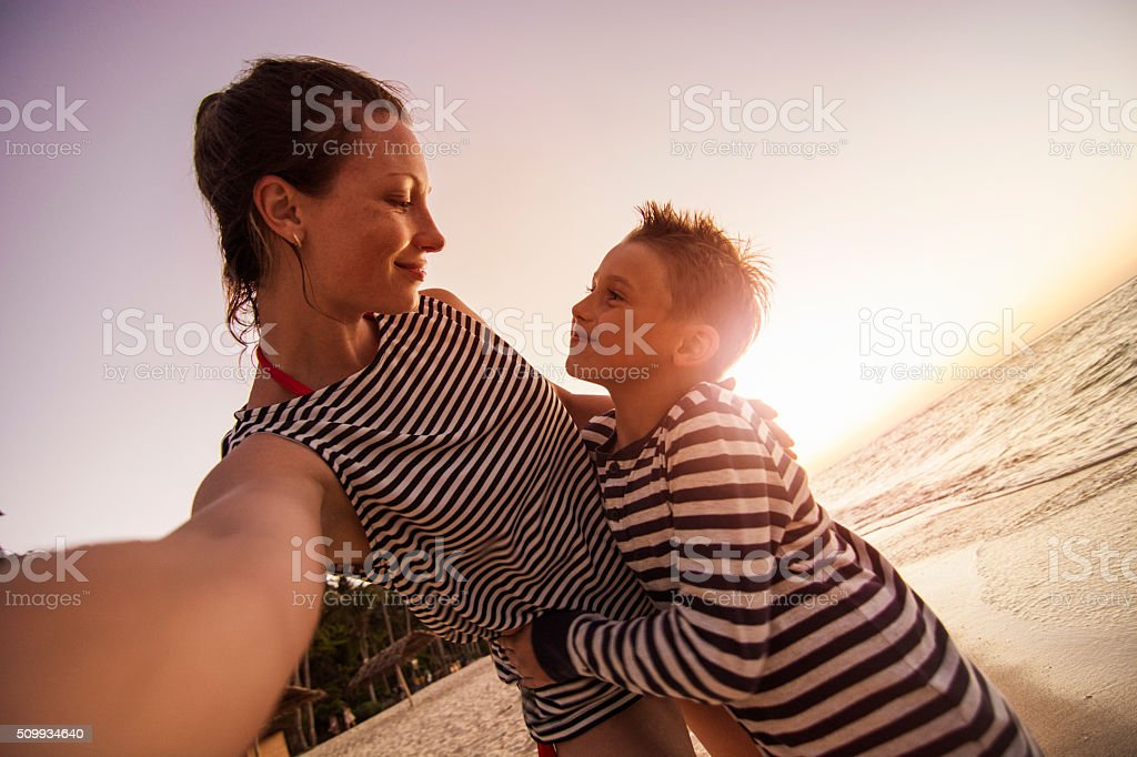 Mother and son taking selfie on the beach stock photo