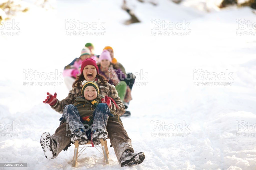 Mother and son (8-10) tobogganing in snow, family in background royalty-free stock photo