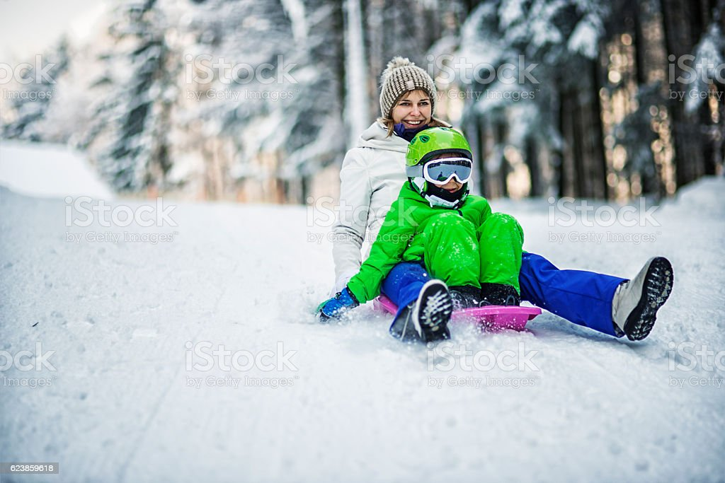 Mother and son tobogganing in winter forest stock photo
