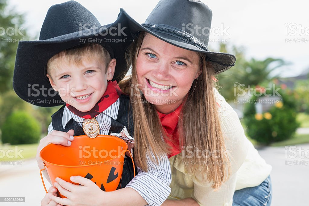 Mother and son trick or treating on Halloween stock photo