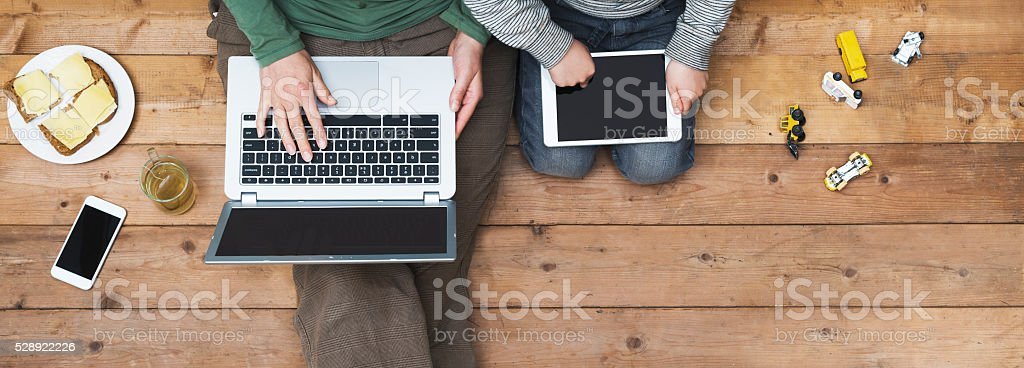 mother and son using laptop and tablet pc stock photo