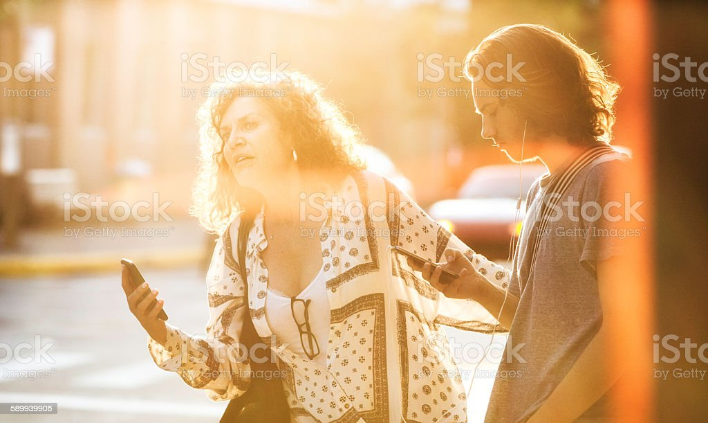 Mother and son waiting for car pool urban sunset lit stock photo
