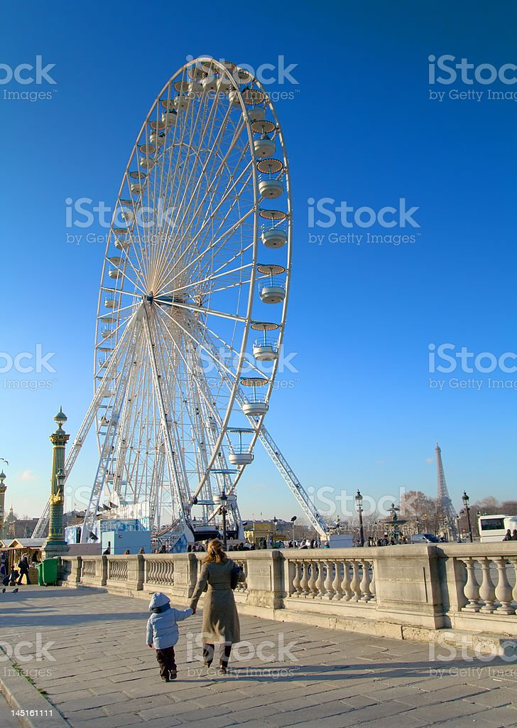 Mother and son walking towards fairground in Paris royalty-free stock photo
