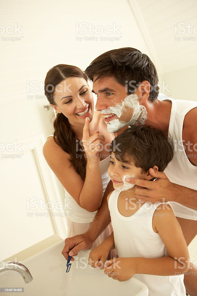 Mother And Son Watching Father Wet Shaving With Razor royalty-free stock photo