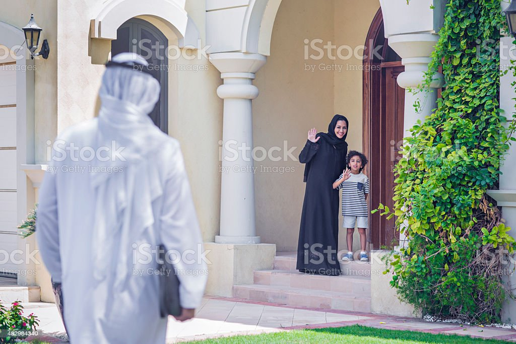 Mother and son welcoming father coming back home. stock photo