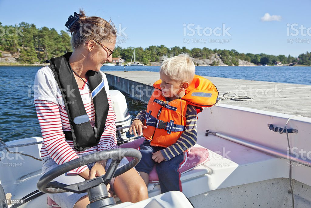 Mother and son with life jackets on board small boat royalty-free stock photo
