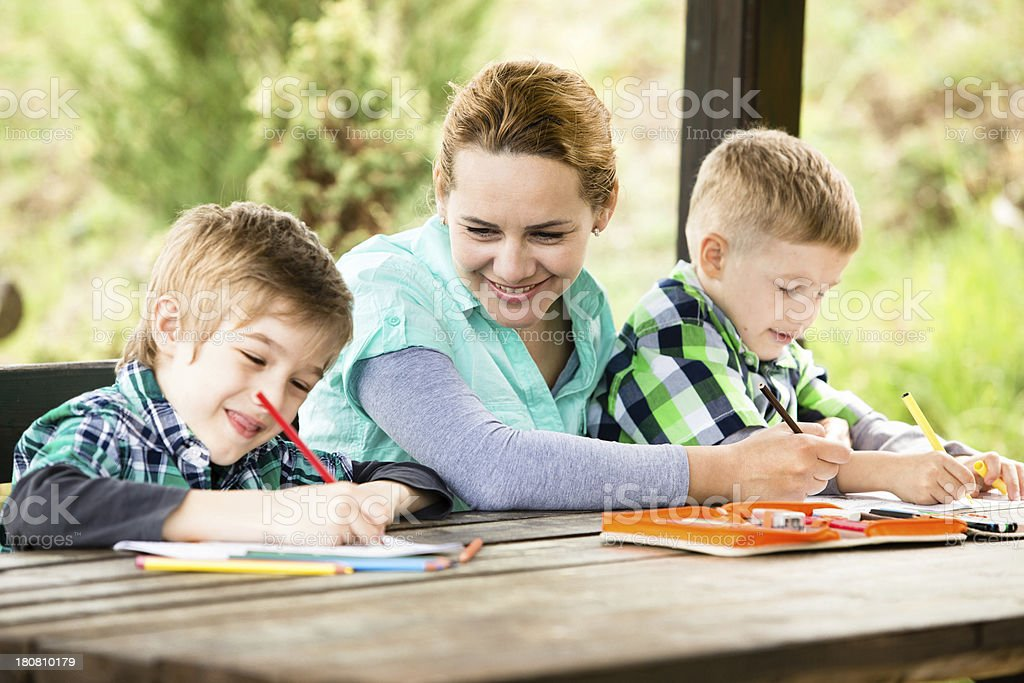 Mother and sons drawing outdoors stock photo