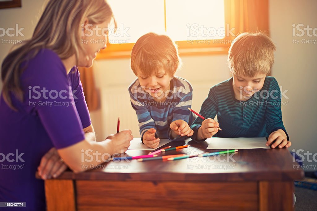 Mother and sons drawing together stock photo
