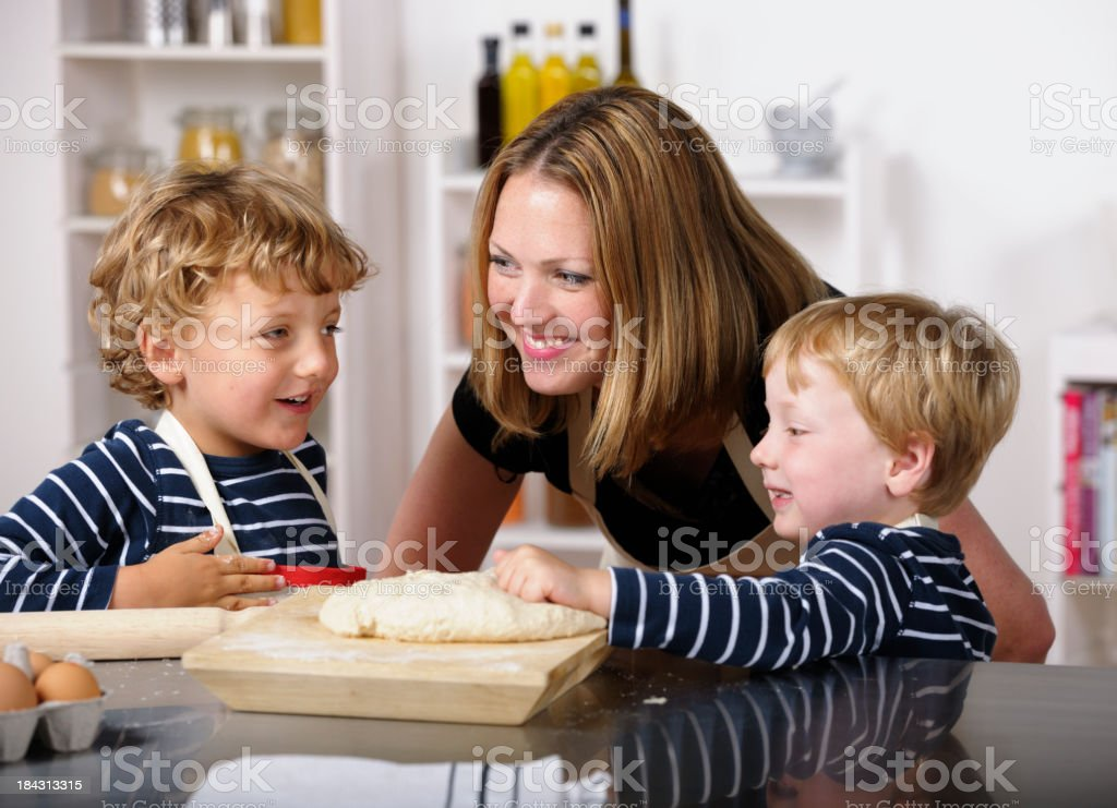 Mother And Sons Having A Discussion While Preparing Bread royalty-free stock photo
