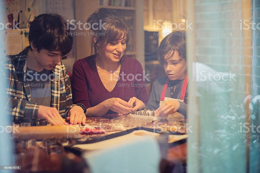 Mother and sons making gingerbread cookie at home through window. stock photo