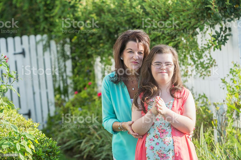 Mother and teenage girl with down syndrome stock photo