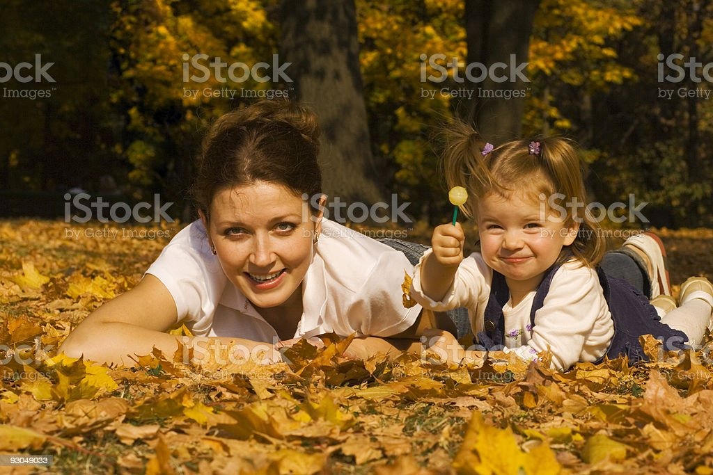Mother and the daughter lay on fallen down leaves royalty-free stock photo