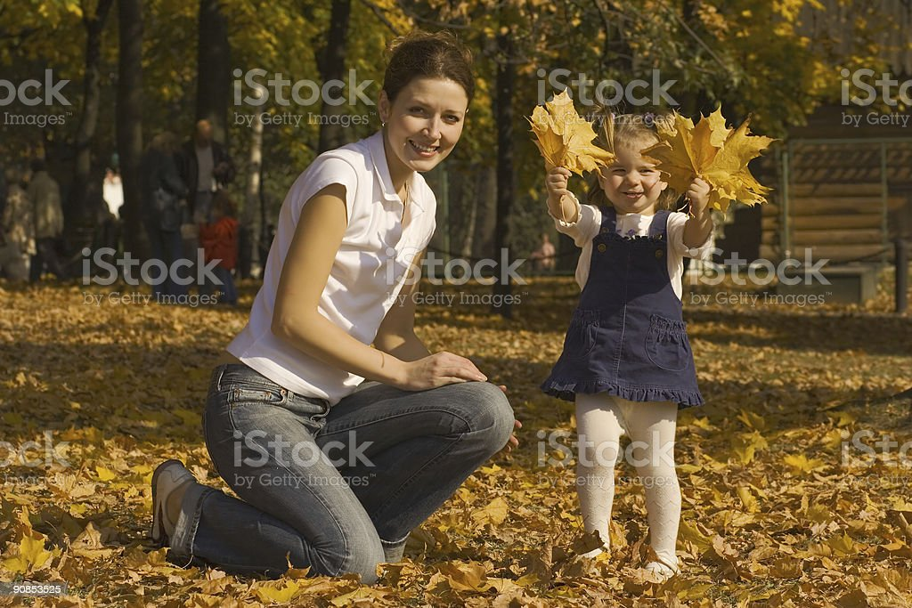 Mother and the daughter on fallen down leaves royalty-free stock photo