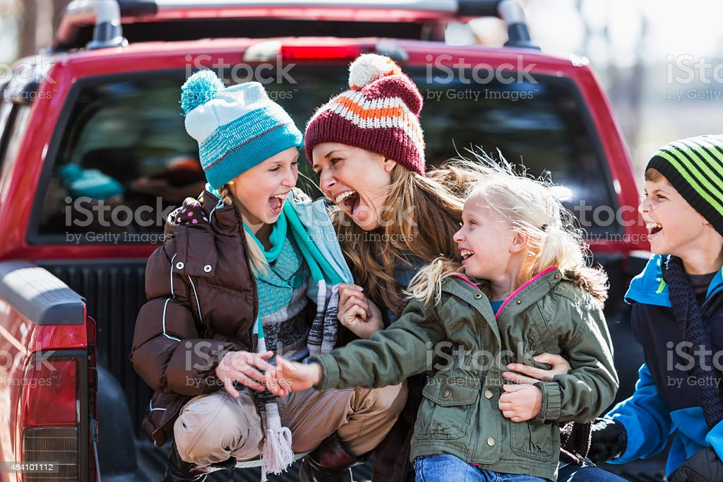Mother and three children having fun outdoors stock photo