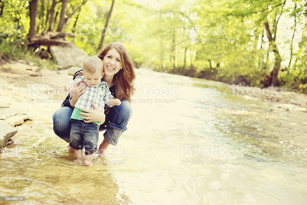 mother and toddler boy outdoors river adventure stock photo