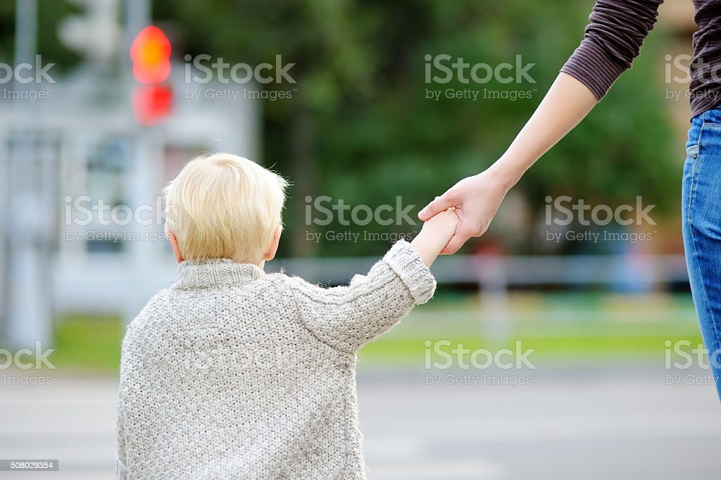 Mother and toddler crossing street on the crosswalk stock photo
