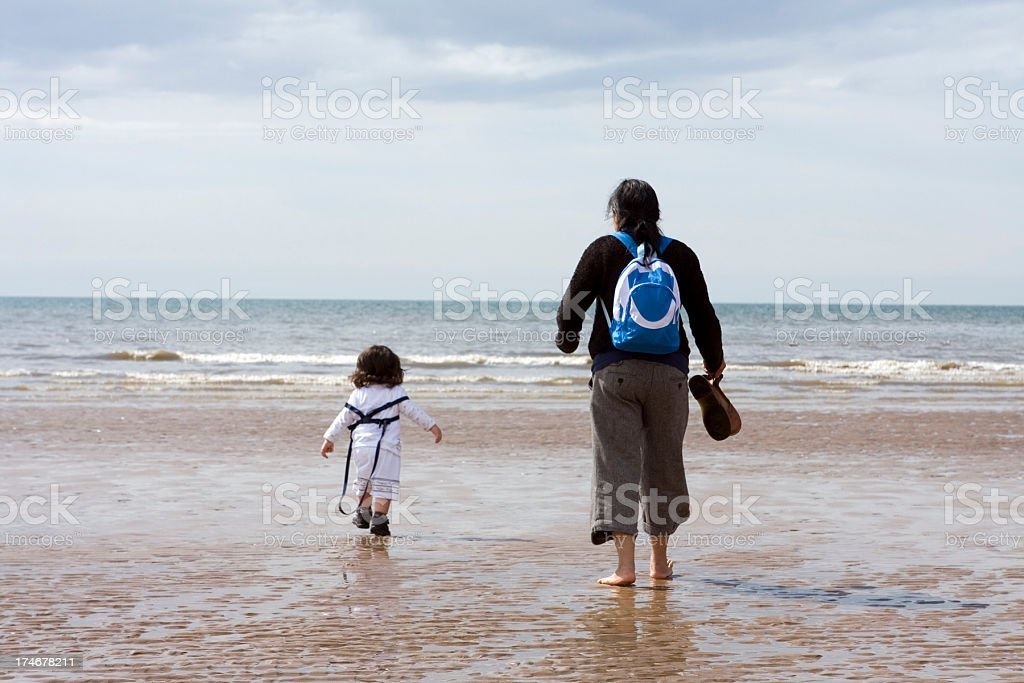 Mother and toddler paddling at the seaside stock photo