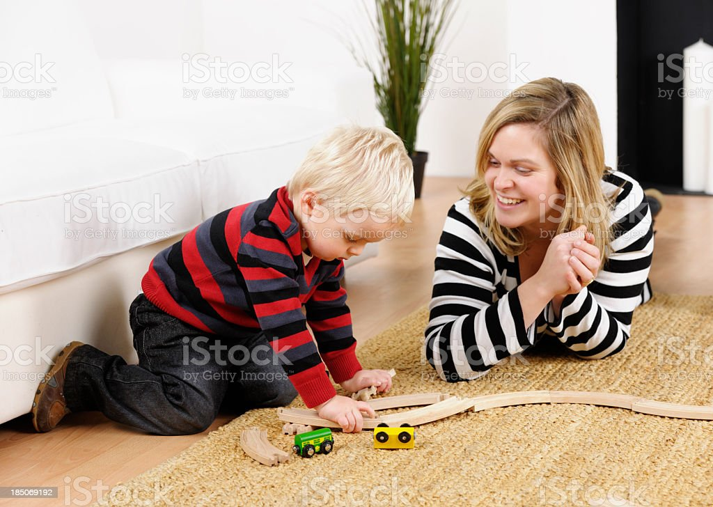 Mother And Toddler Playing With Train Set In The Lounge stock photo