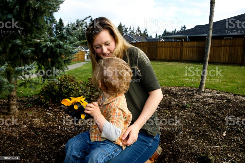 Mother and toddler son playing with toy trucks stock photo