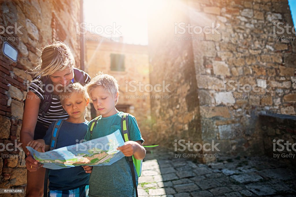 Mother and tourist sons checking map in an Italian town stock photo