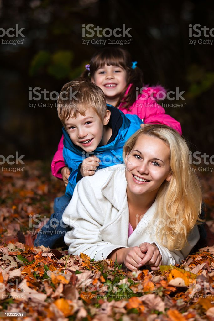Mother and two children playing in the woods at autumn royalty-free stock photo
