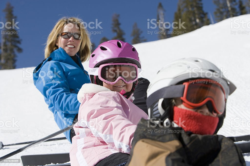 Mother and two children taking a break from snow skiing royalty-free stock photo