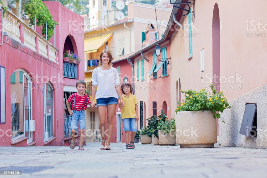 Mother and two children, walking hand in hand on a colorful street in France village Villefrance stock photo