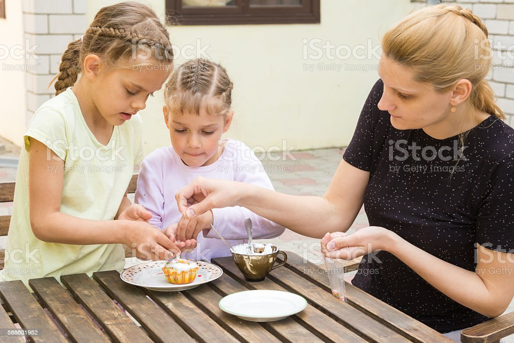 Mother and two daughters sprinkled cupcakes Easter candy sprinkles stock photo