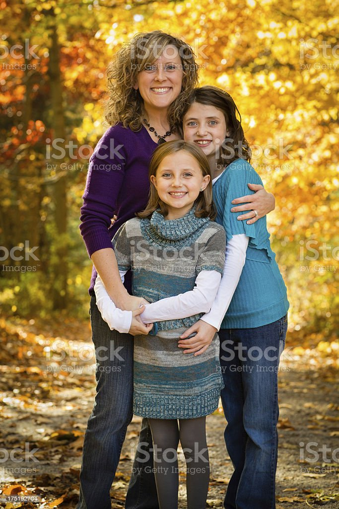 Mother and Two Daughters Standing in Beautiful Autumn Woods royalty-free stock photo