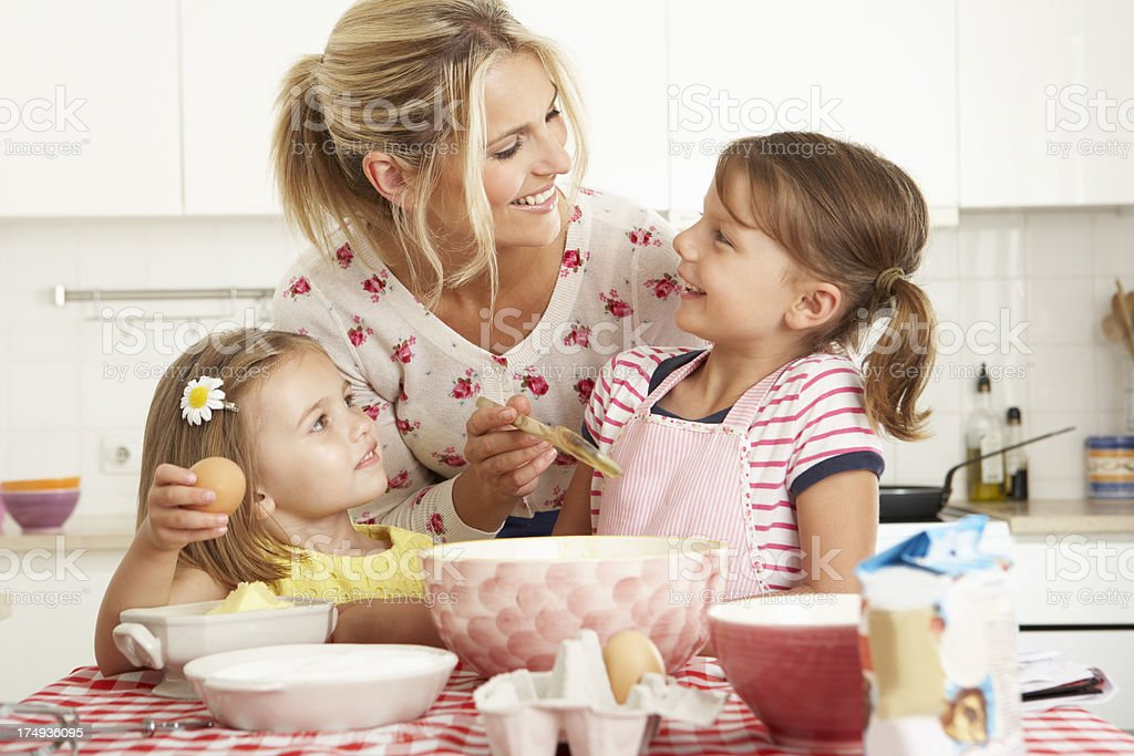 Mother and two girls baking a cake in the kitchen royalty-free stock photo