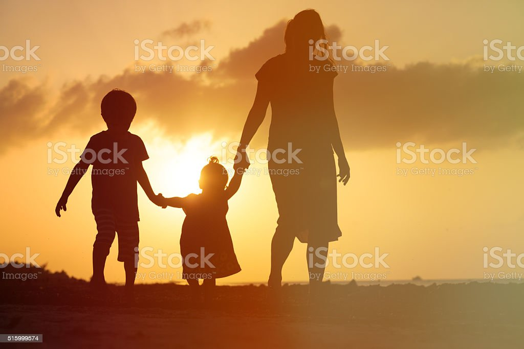 mother and two kids walking at sunset beach stock photo