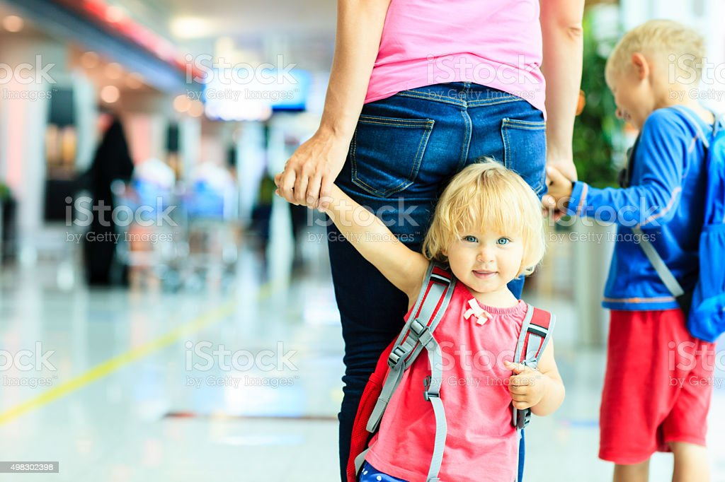 mother and two kids walking in the airport stock photo