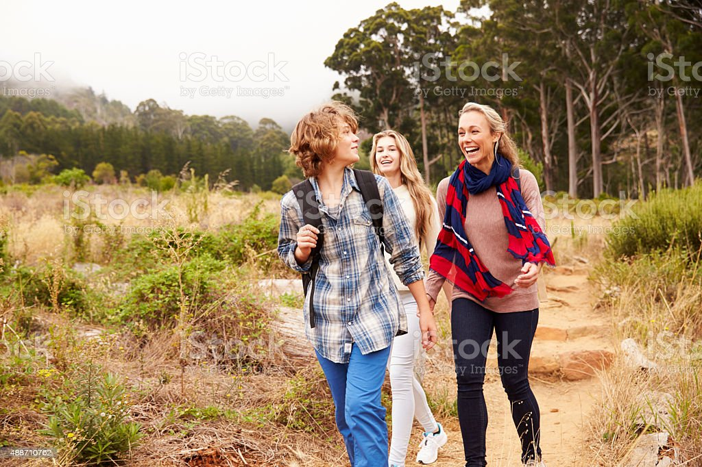 Mother and two kids walking on a forest trail stock photo