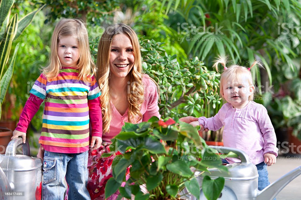 Mother and two little girls gardening stock photo