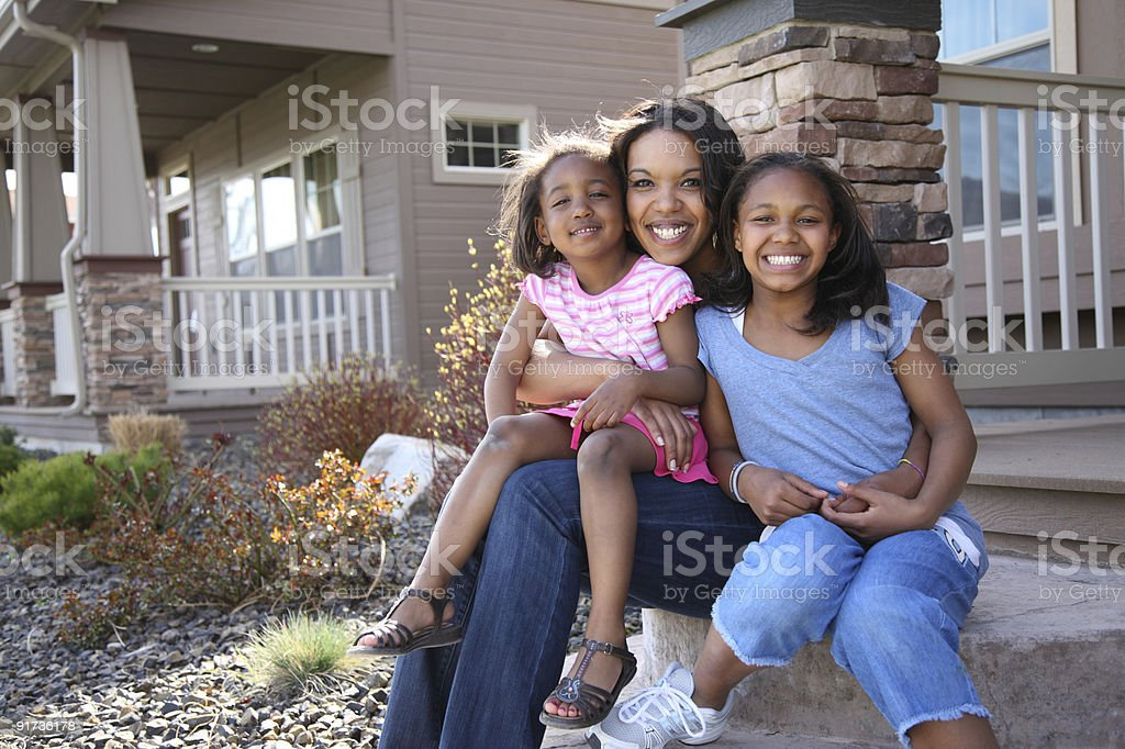 A mother and two little girls smiling on a front porch royalty-free stock photo