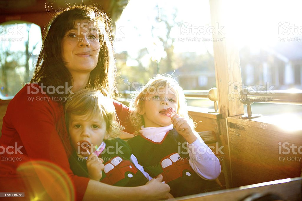 A mother and two toddler boys ride on a trolley. royalty-free stock photo