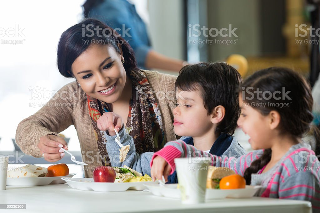 Mother and young children having meal in charity soup kitchen