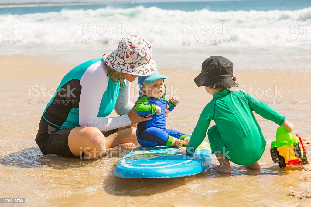 Mother and Young Children Playing at the Beach stock photo