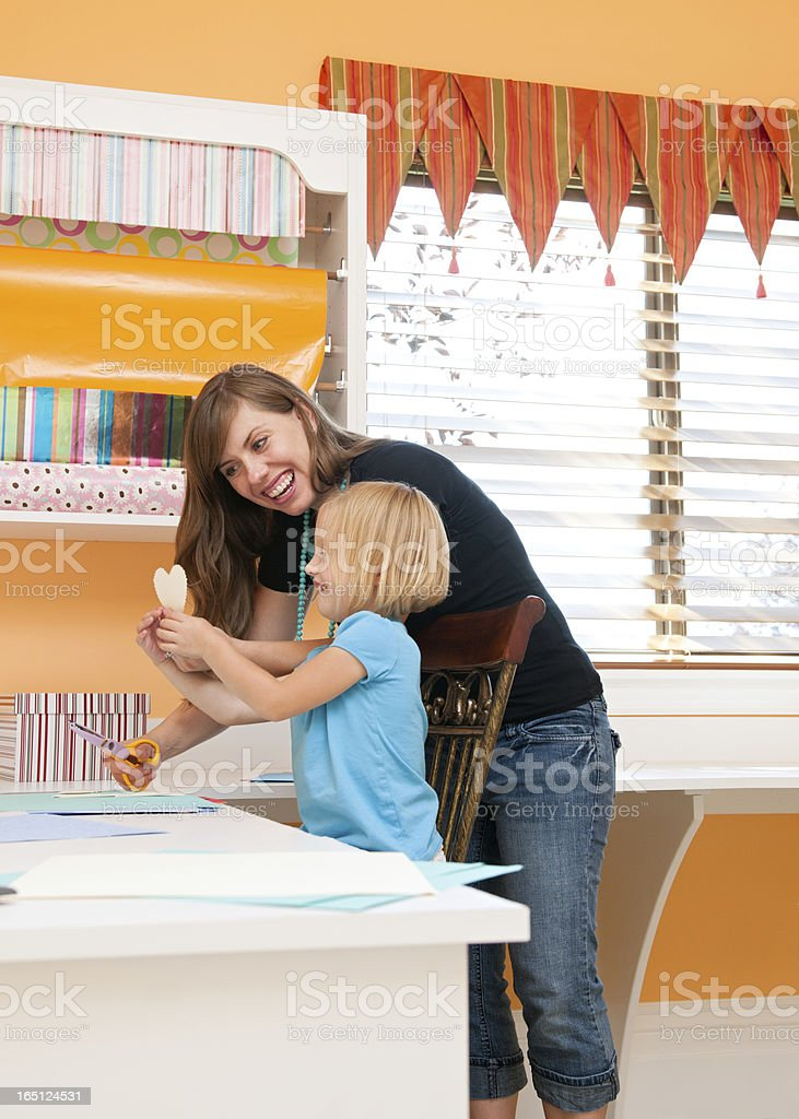 Mother and young daughter work on crafts. stock photo